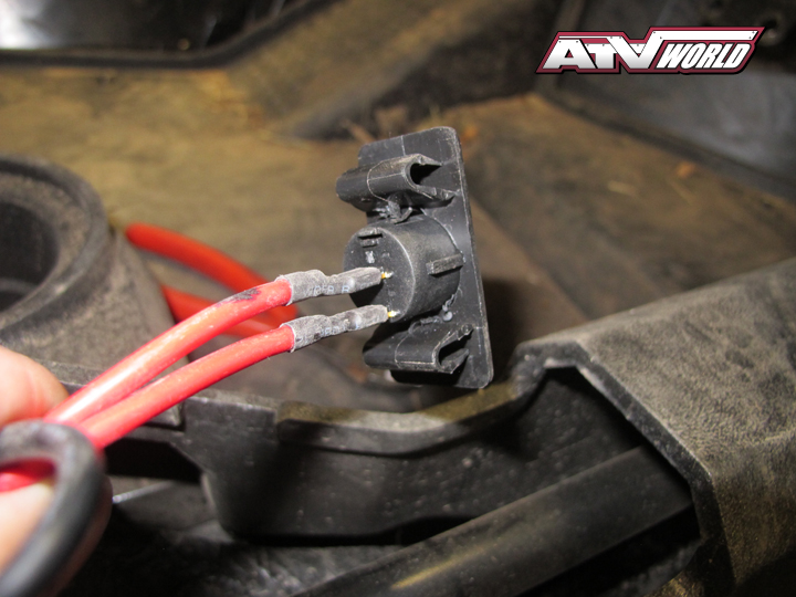 """Probably the trickiest part of the install will be determining where you want to install the round toggle switch. The wires from the switch can be simply pulled off making it easy to mount. The switch features a plastic retention system and requires a ½"""" hole whereby the switch can be simply pushed into place. We choose to use one of the Arctic Cat Trail's removable rectangular toggle switch covers. We drilled a hole in the middle of the plate to mount the Biltrite switch. Note: the switch has a raised rib on one side to keep the switch from rotating in the hole. Take your time and carefully creating a matching notch in the plastic where you'll be mounting the switch using a small utility knife to accept the ridge."""